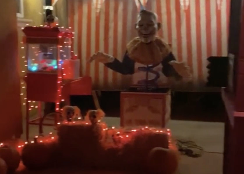 A giant clown jack-in-the-box sits next to a popcorn machine covered in orange lights