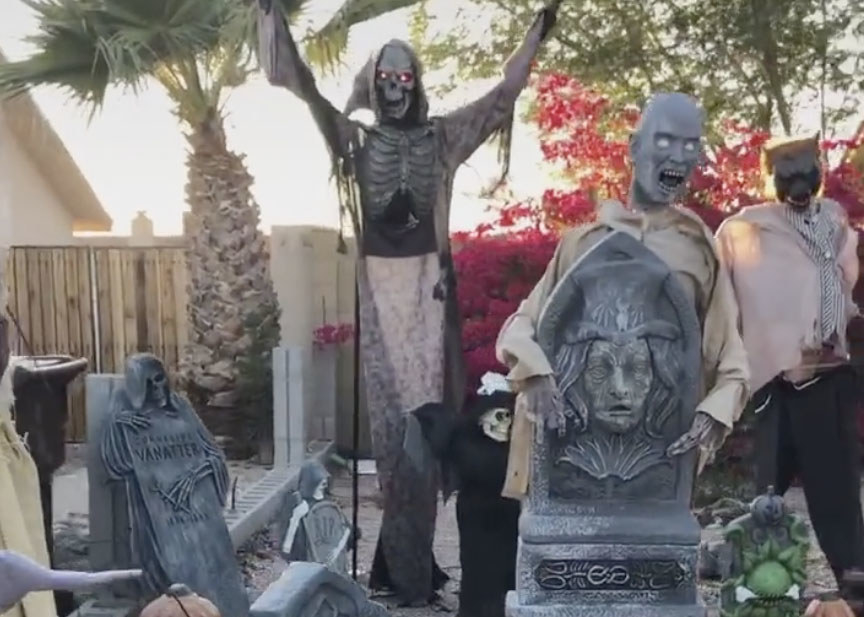 A yard filled with eerie gravestones, the grim reaper and other spooky people