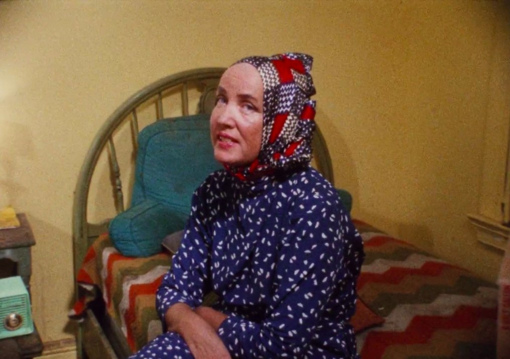 Edith Bouvier Beale sitting on her bed in 'Grey Gardens'
