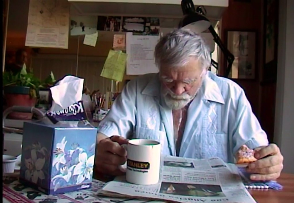 A terminally ill man sitting at a table drinking coffee and eating a pastry in 'The End'