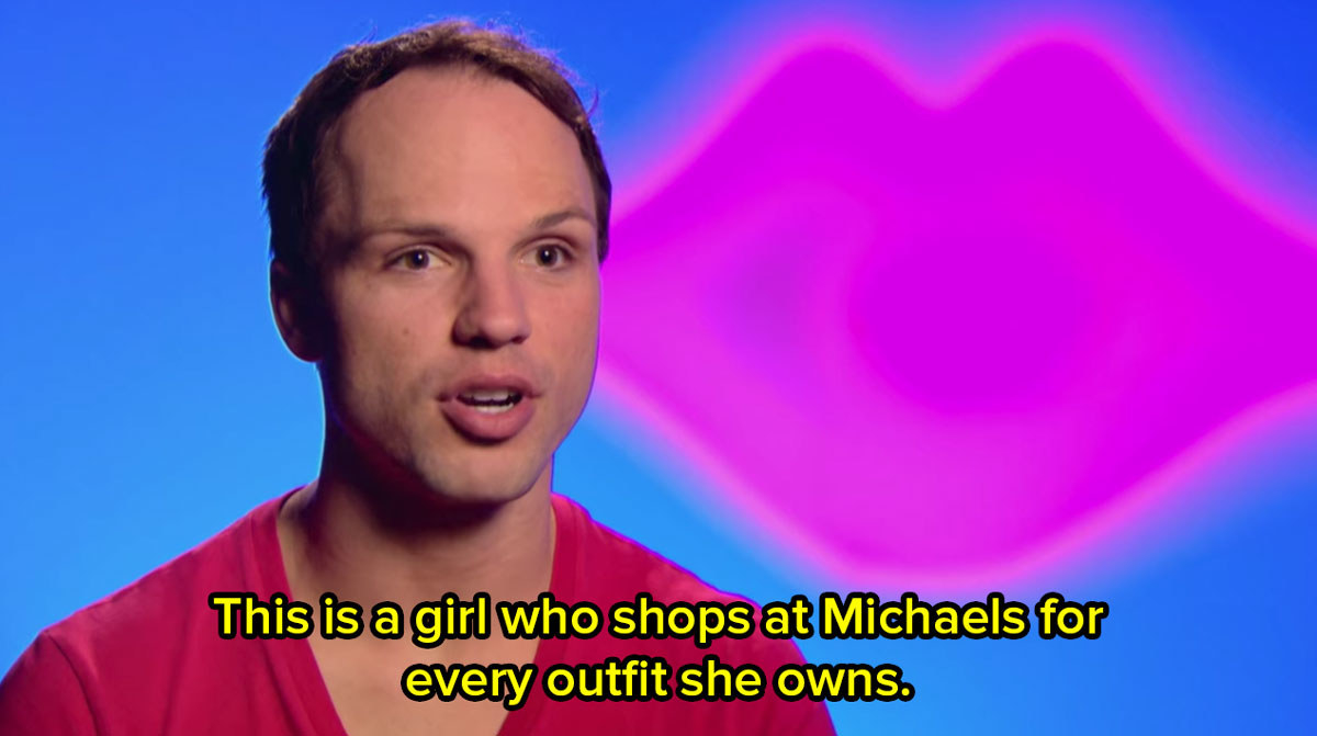 A close up of a contestant from Drag Race in front of a bright blue background giving a talking head interview and saying this is a girl who shops at Michaels for every outfit she owns