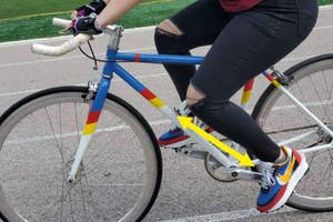 A person riding a bike with shoes that have the same exact color scheme as their bike.