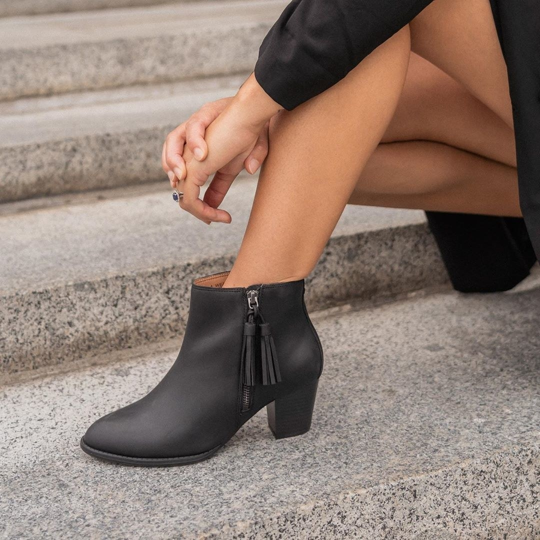 model wearing black booties with tassel size zipper