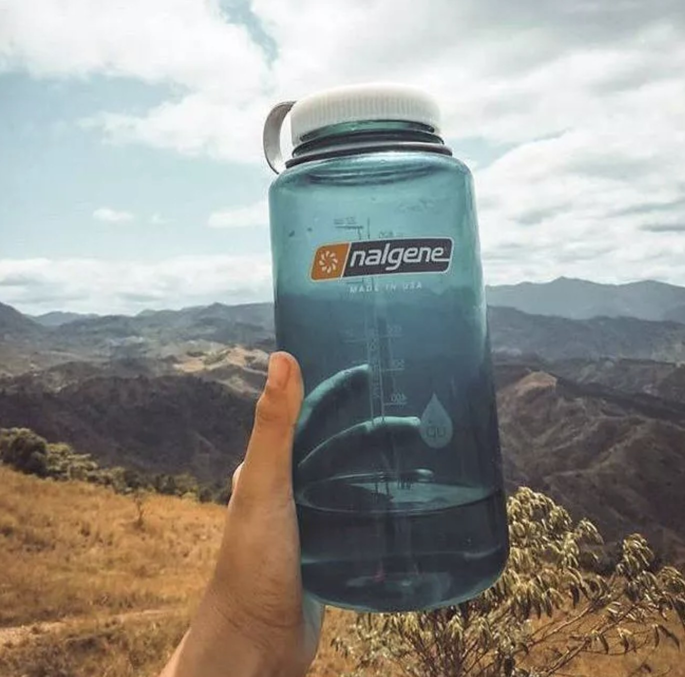 a teal water bottle with a grey cap in front of a serene mountain landscape