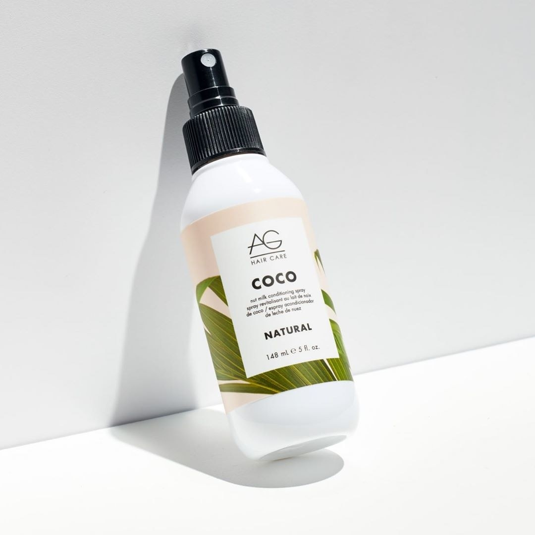 A bottle of hair conditioning spray leaning against a wall