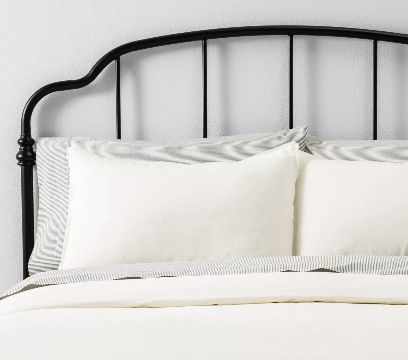 an ivory linen set on a black wire bed