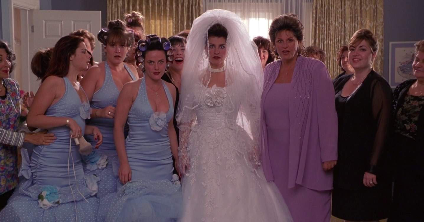 """Toula dressed in a wedding dress next to her mother and bridesmaids in """"My Big Fat Greek Wedding"""""""