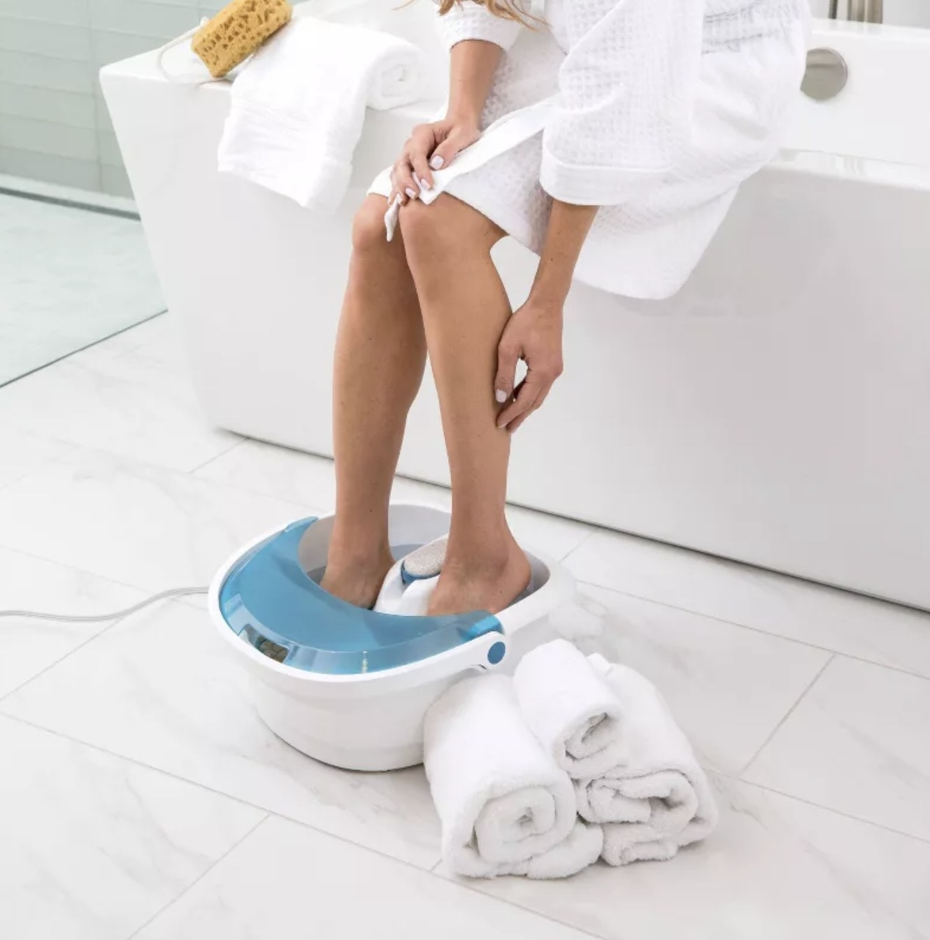 a person with their feet in a blue and white foot spa