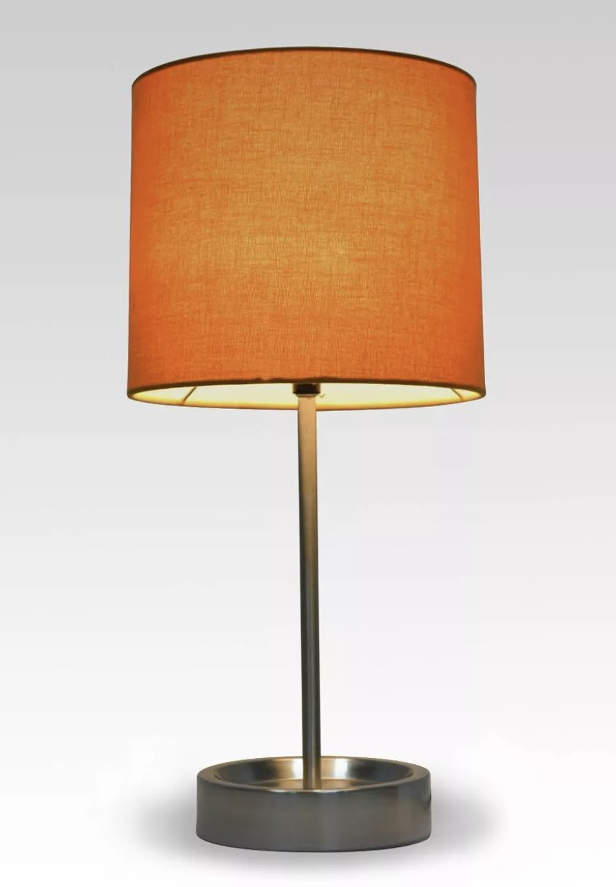 a brass lamp with an orange lampshade