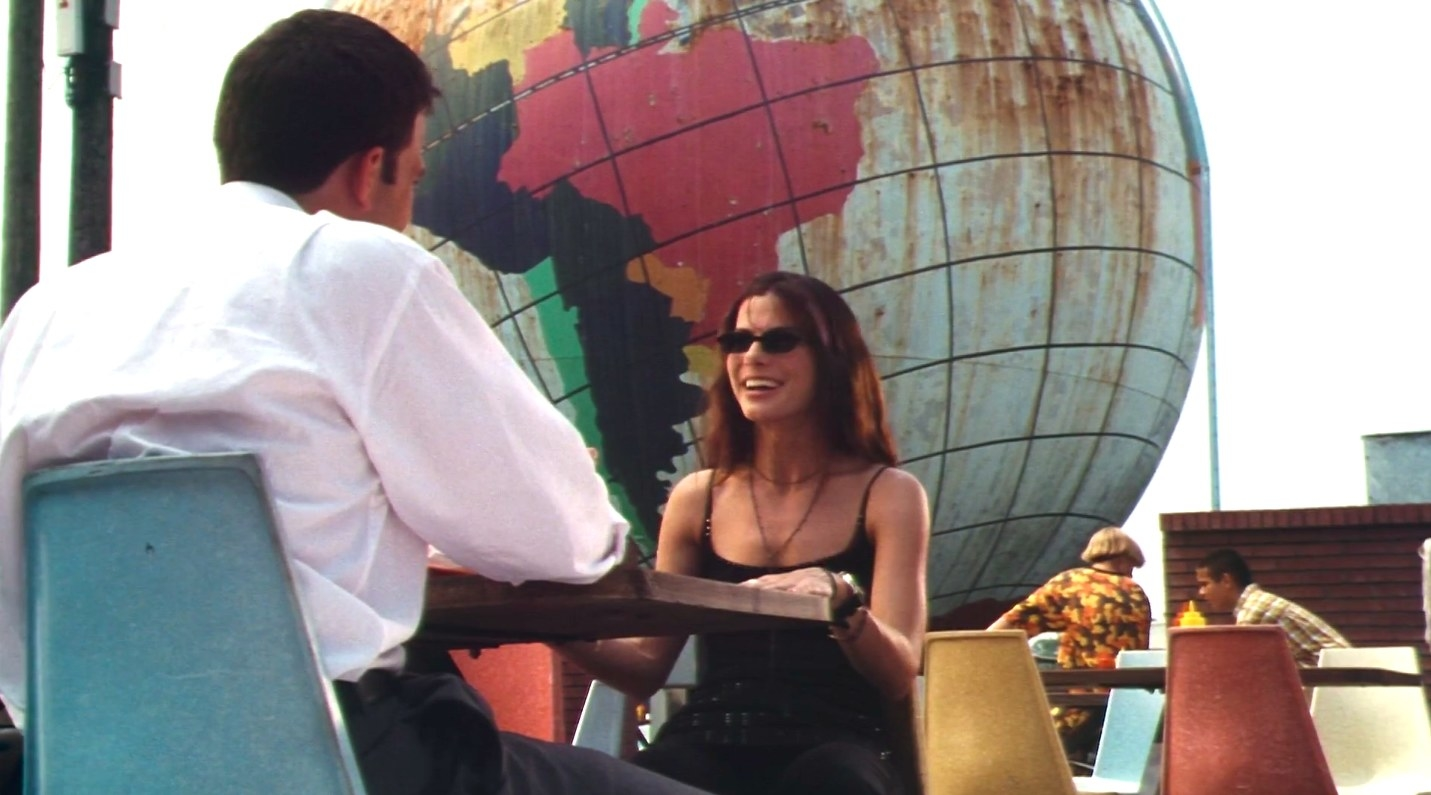 """sandra bullock sits in front of a globe in """"Forces of Nature"""""""
