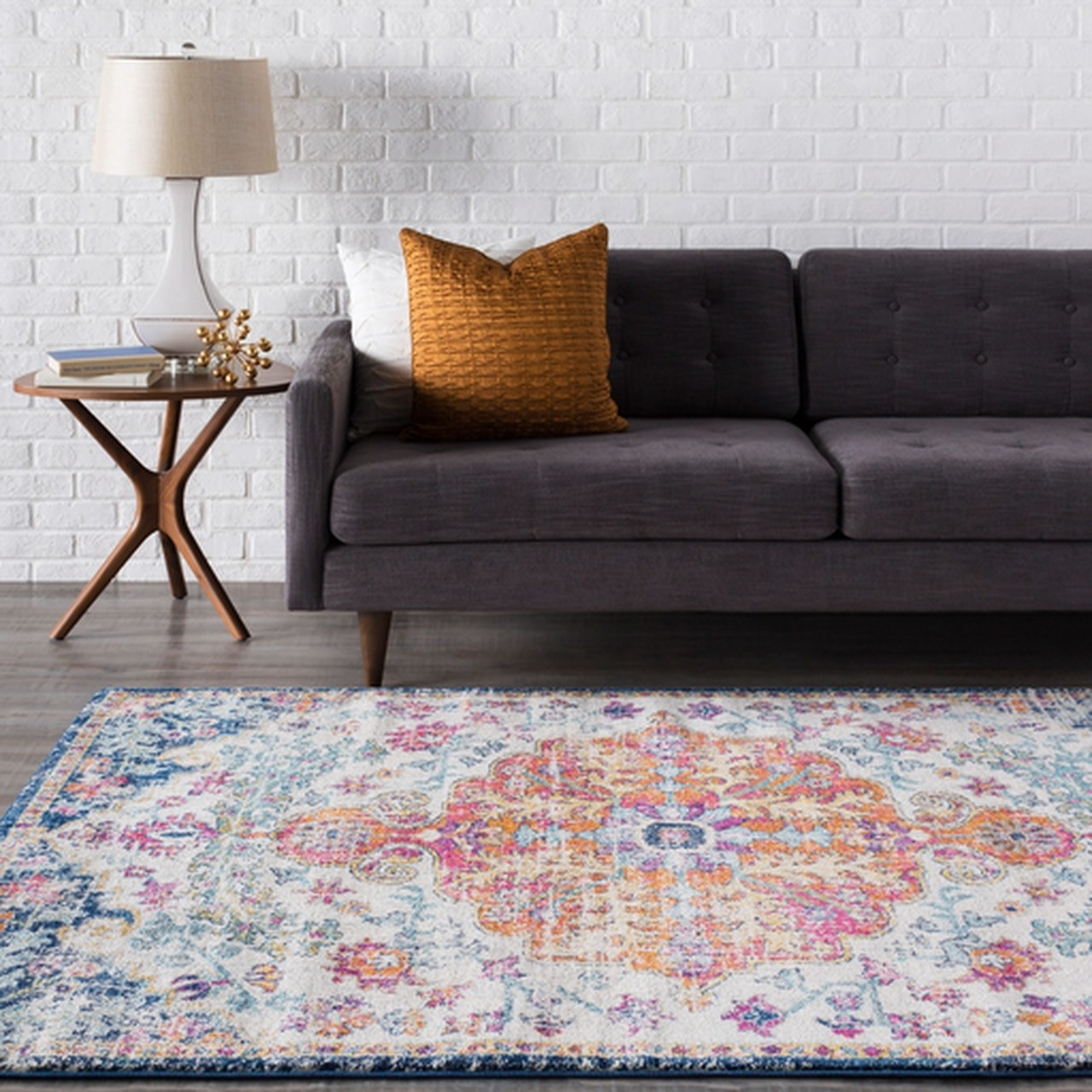 an area rug with a design including light blue, navy blue, white, pink, orange and yellow