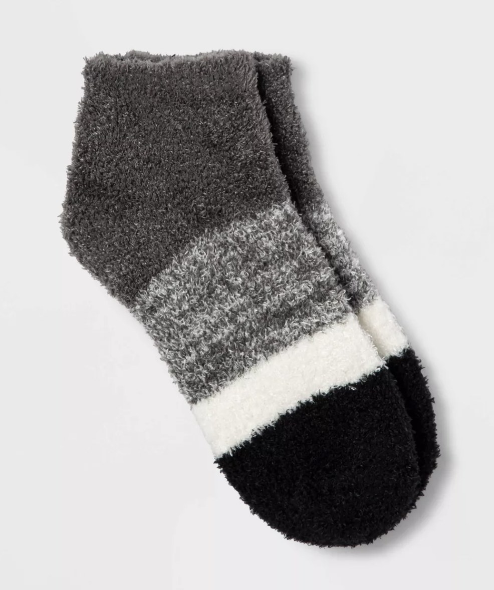 a pair of fuzzy socks with grey, heather grey, white, and black stripes