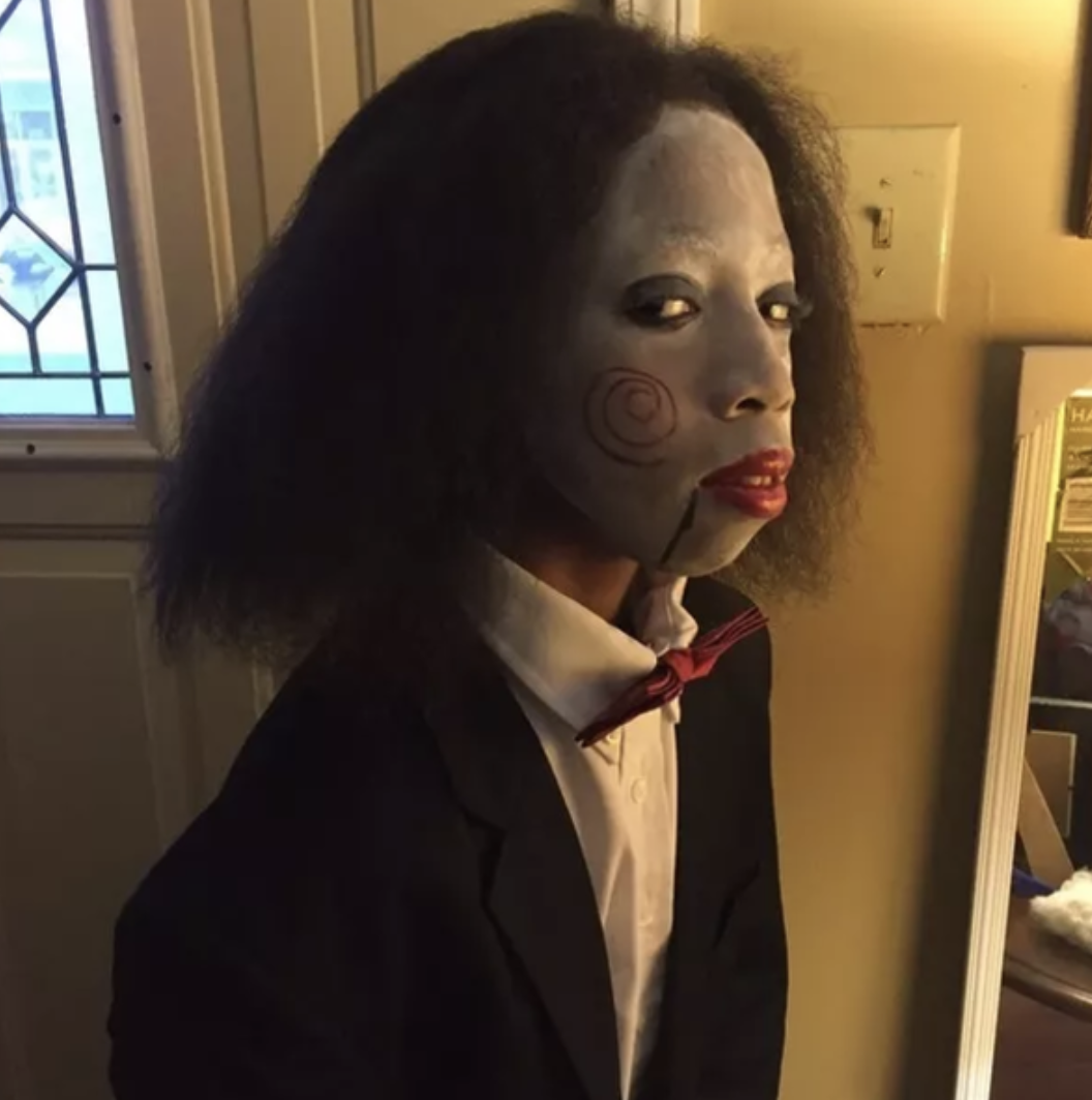 "Someone dressed in a suit and bowtie with face paint that makes them look like Jigsaw from the ""Saw"" franchise"