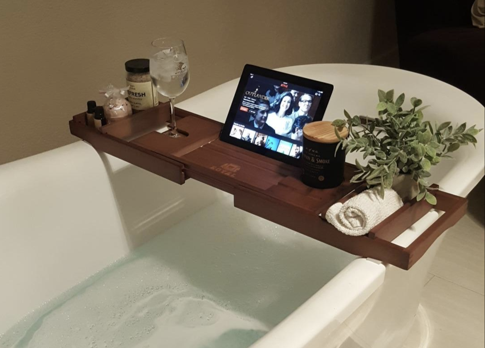 Reviewer image of a wooden bath caddy holding an iPad, washcoth, plant, candle, wine glass, bath salts