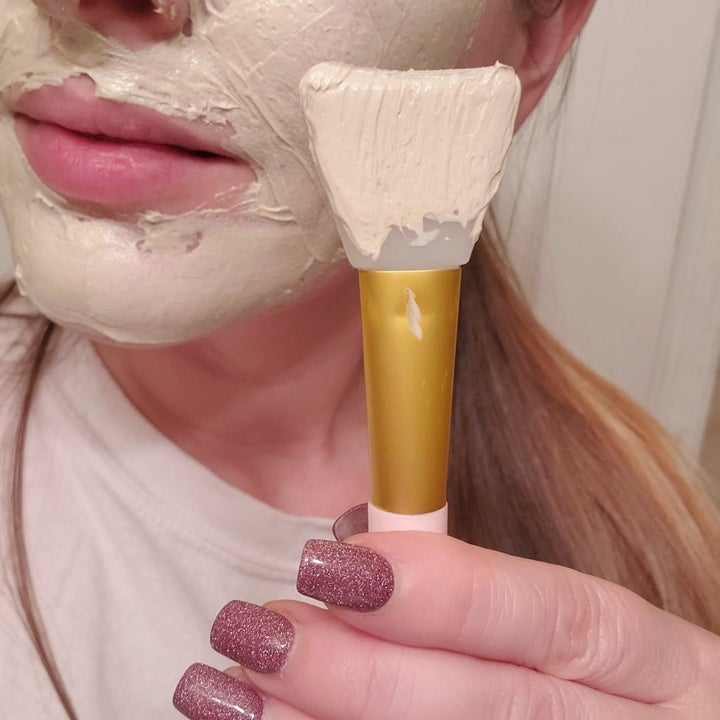 "A reviewer with a thick layer of mask on their face, holding up the spatula-like applicator ""brush"""