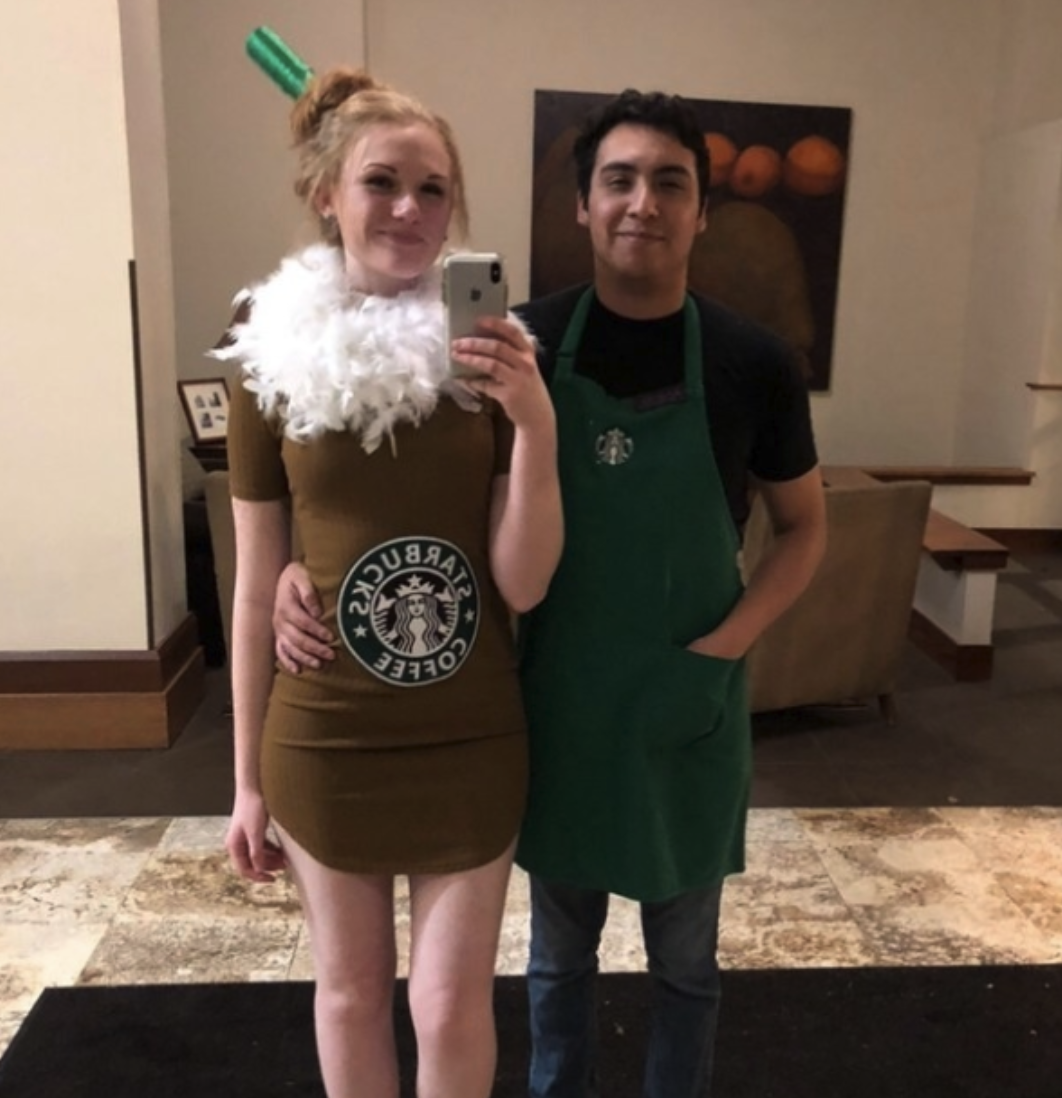 One person wearing a green Starbucks apron, and another dressed in all brown with feathers around their neck and a printed-out Starbucks logo on their stomach to look like a Frappuccino