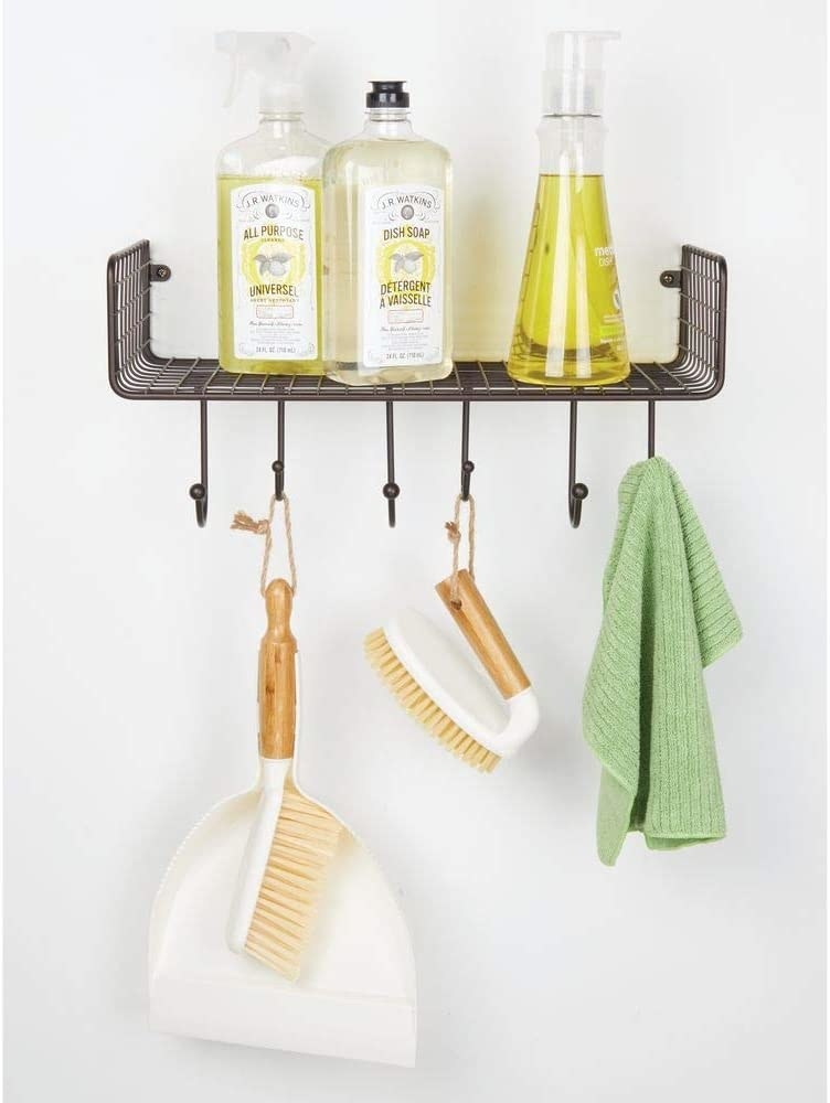 The white dustpan and brush hung from a hook