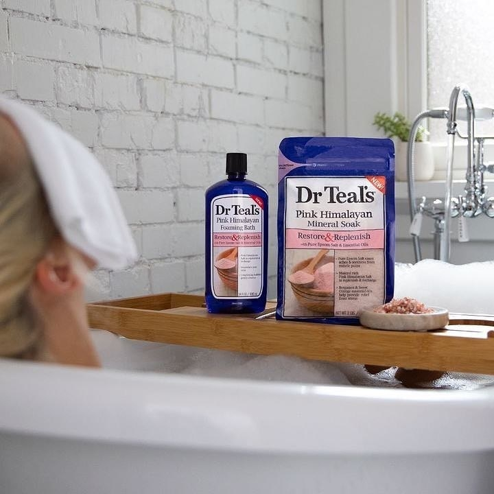 The pink mineral soak next to woman taking a relaxing bath