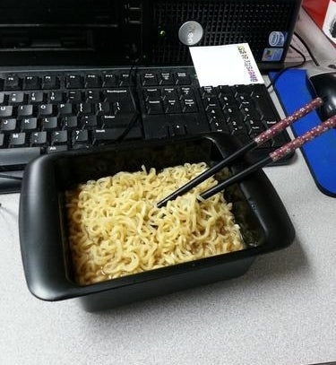 A reviewer's cooked ramen in the black rectangular bowl