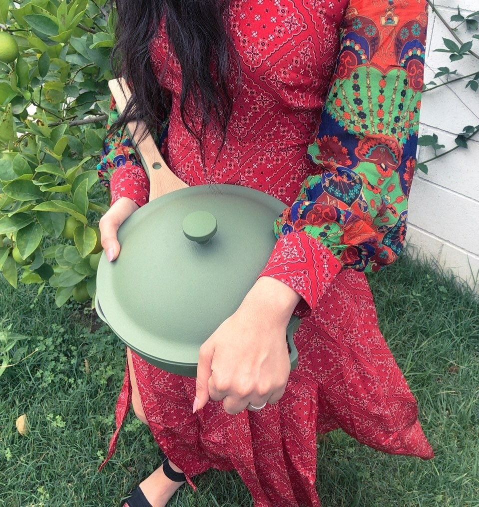 a model holding the matte sage green pan with a wooden handle and a lid