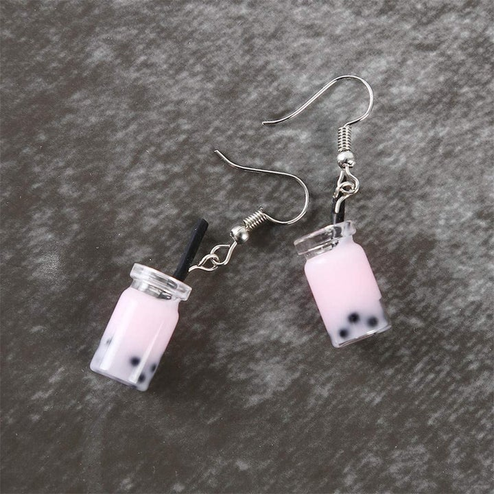 The small dangle earrings with charms that look like cups of pink bubble tea with a straw