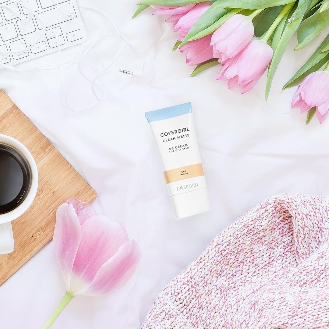 CoverGirl BB Cream on desk surrounded by flowers, coffee and other items