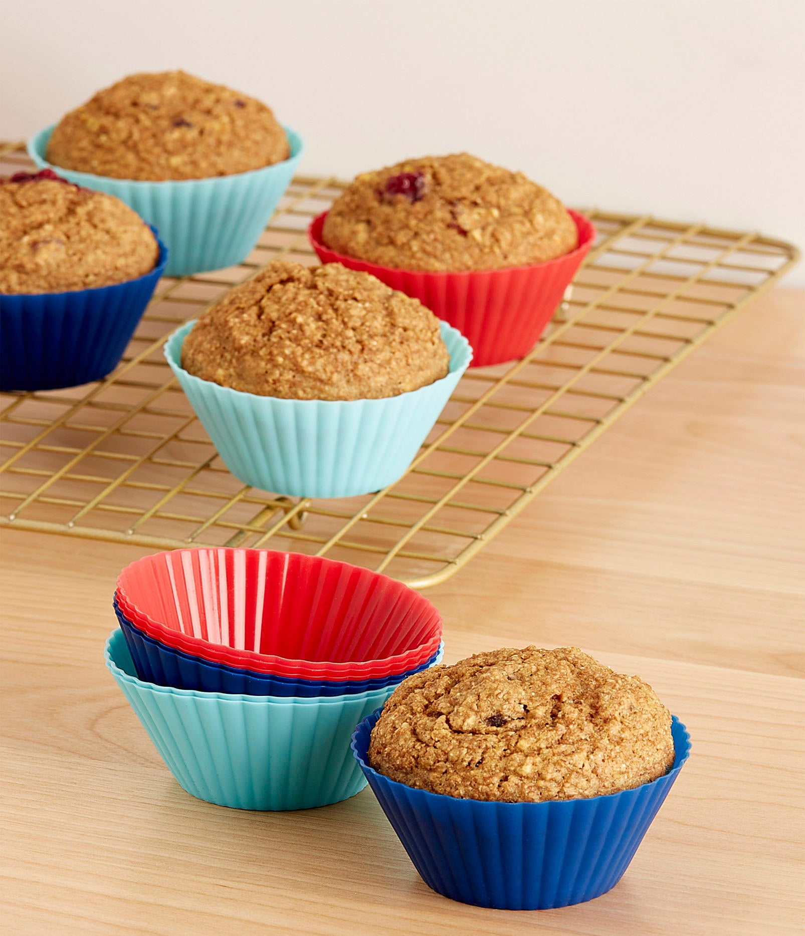 A set of silicone muffin liners with muffins on a baking rack