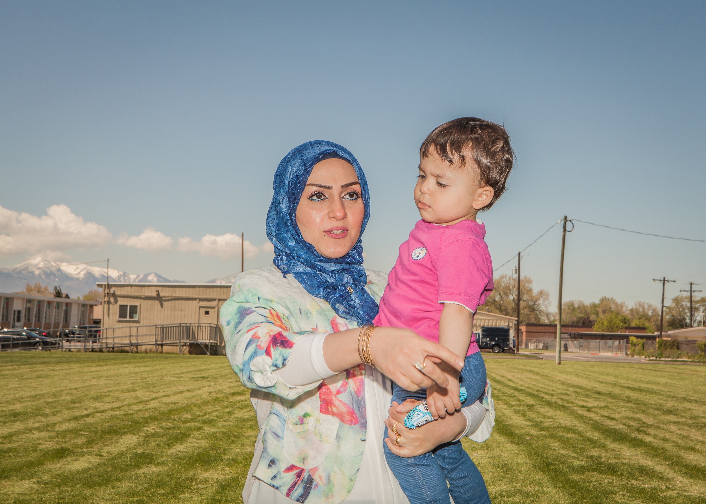 A woman in a hijab holding a child