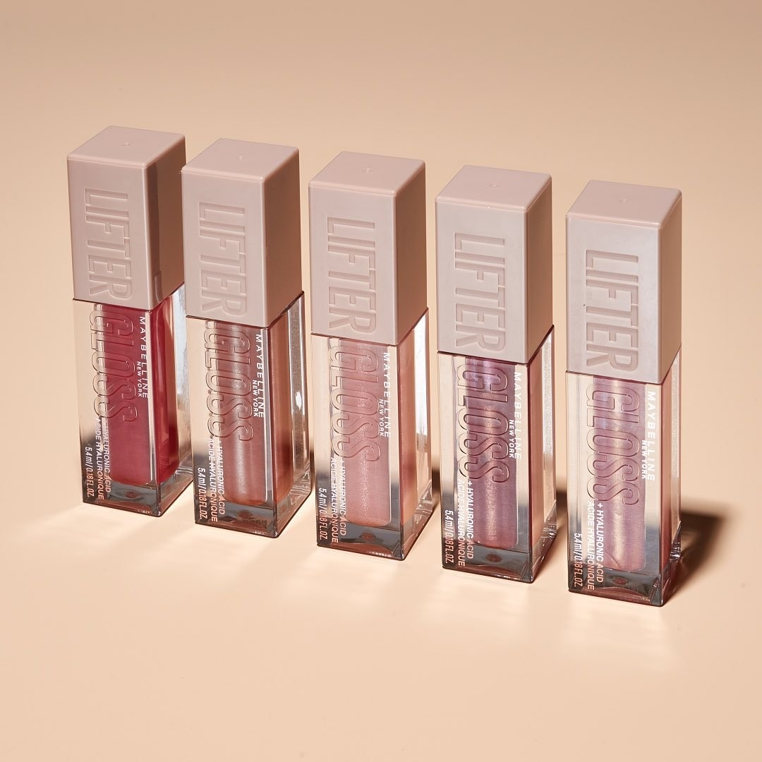 Maybelline lifter gloss shades on peach background