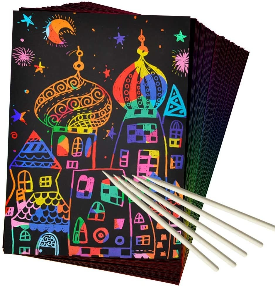 the scratch art with a rainbow castle on it and wooden drawing utensils