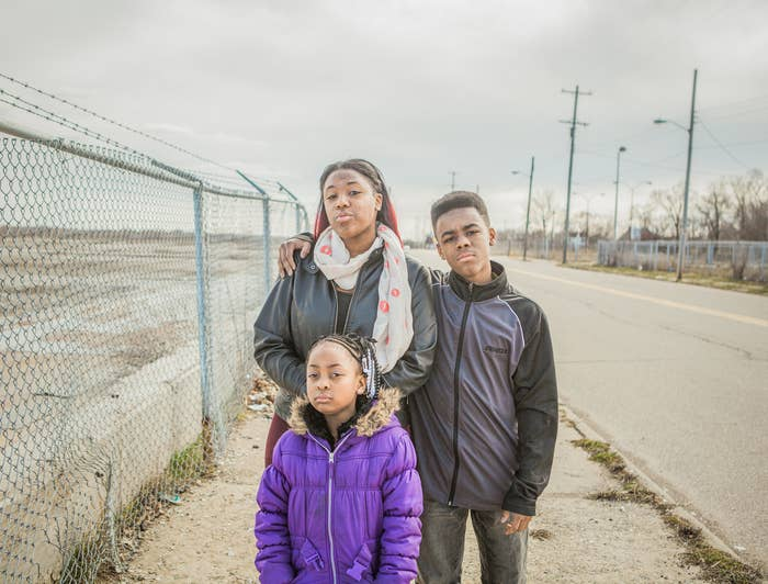 Three young people in coats on a sidewalk in Flint Michigan with a barbed wire fence