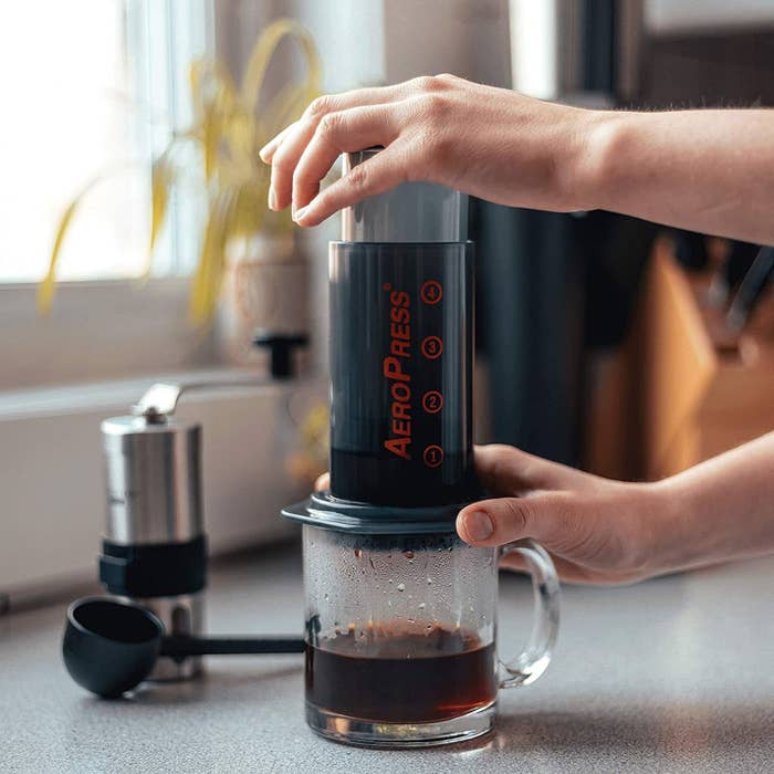 A person using an Aeropress in their kitchen