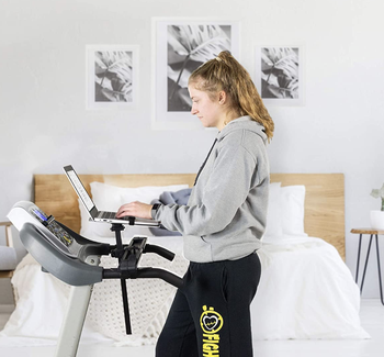 A personal walking on a treadmill with their laptop propped in front of them