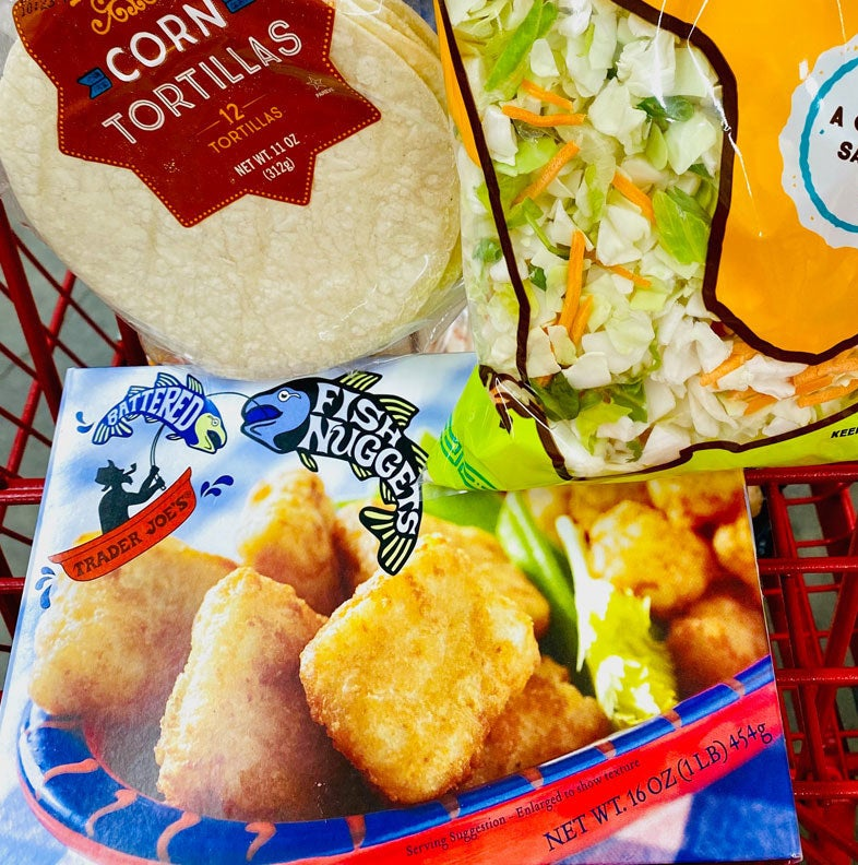 A box of Trader Joe's battered fish nuggets with a bag of slaw and tortillas in a cart.