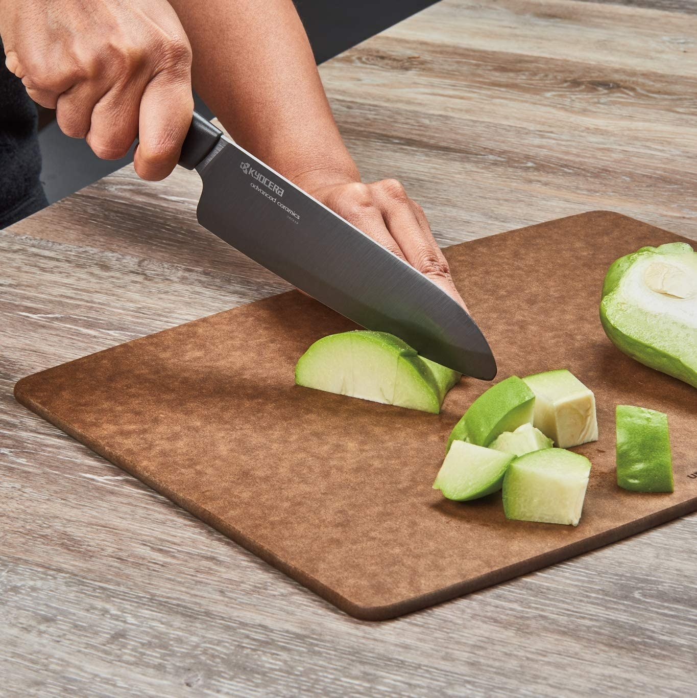 Person cutting vegetables with black knife
