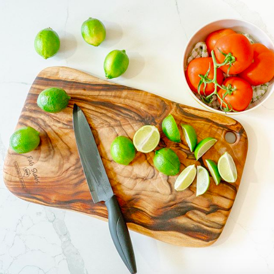 Natural wood cutting board with chopped limes on top