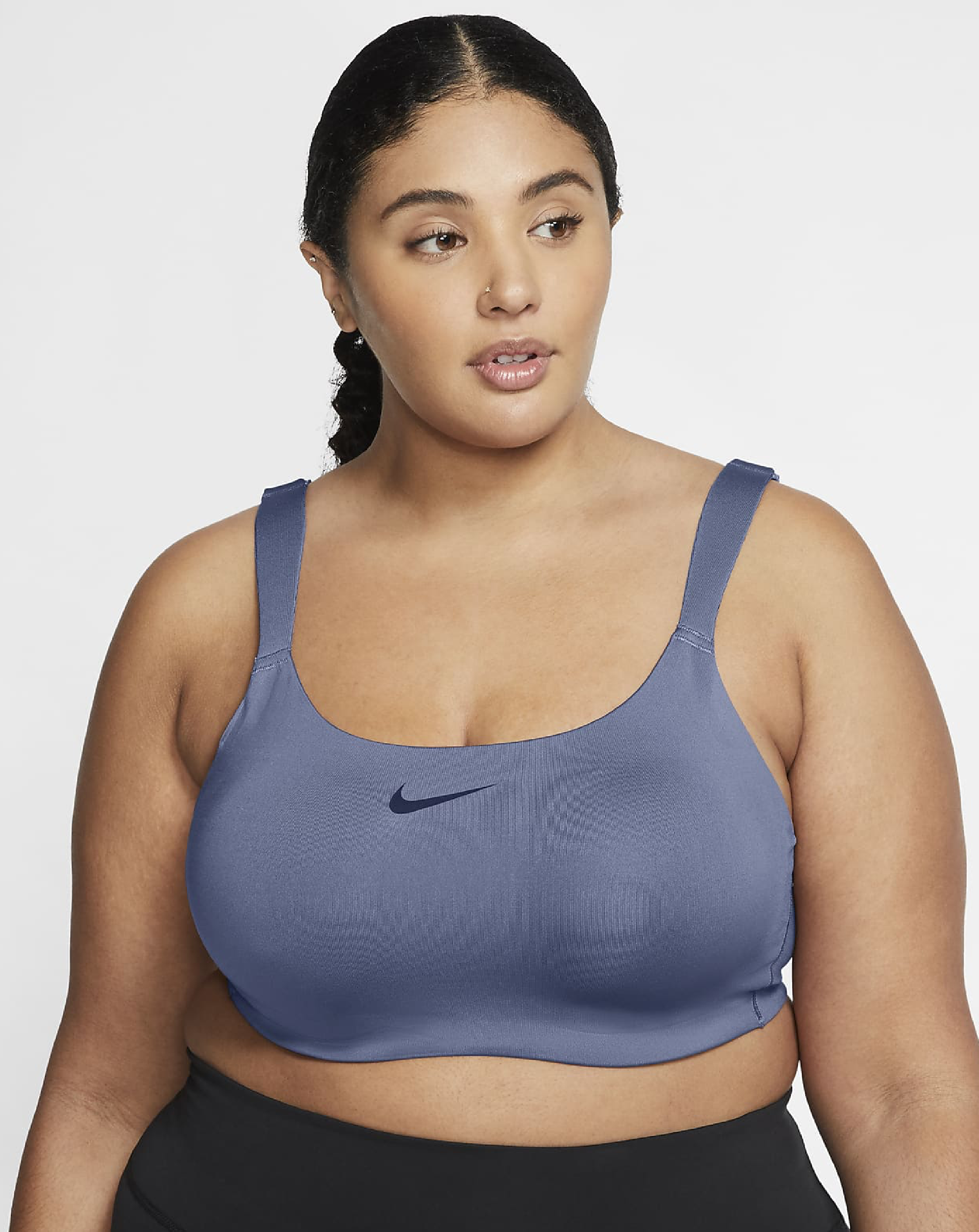 A plus sized model wearing the grey bra with a black Nike swoosh in the center