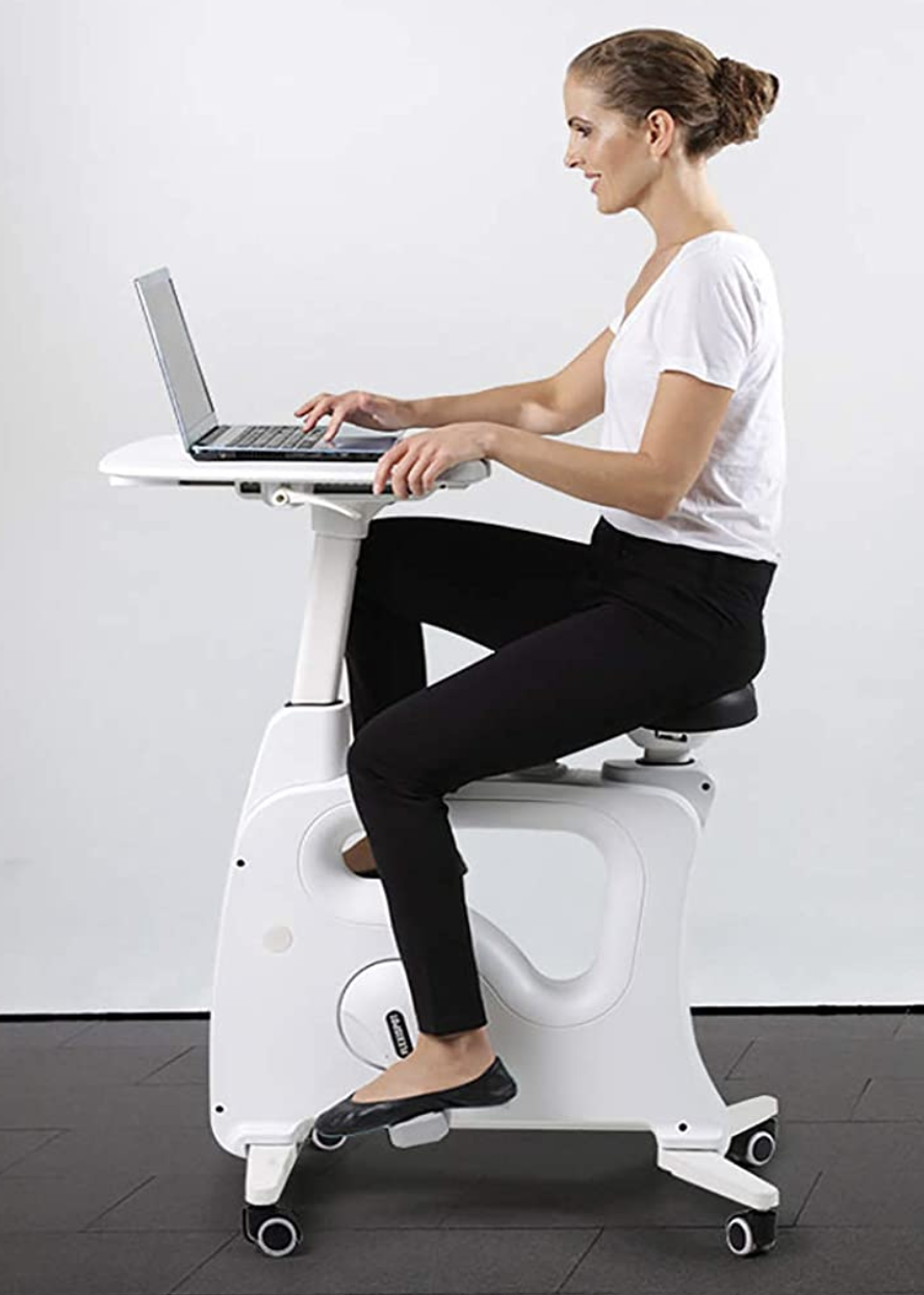 A model on a white bike desk with a tray steadying their laptop