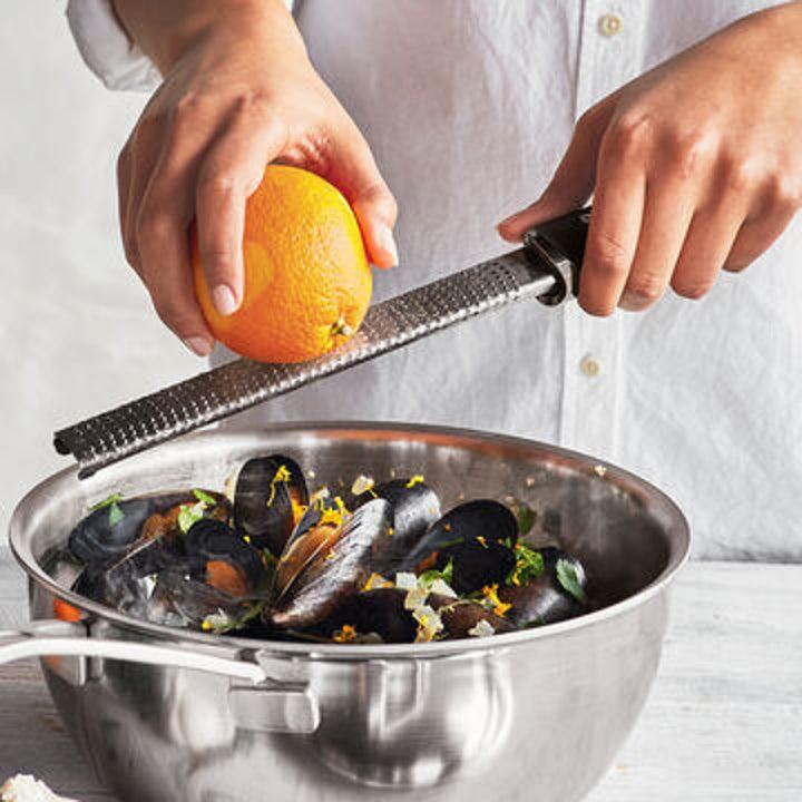 Person adding orange zest to a dish