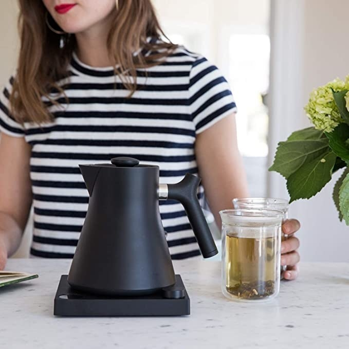 A model with the black kettle and a cup of tea