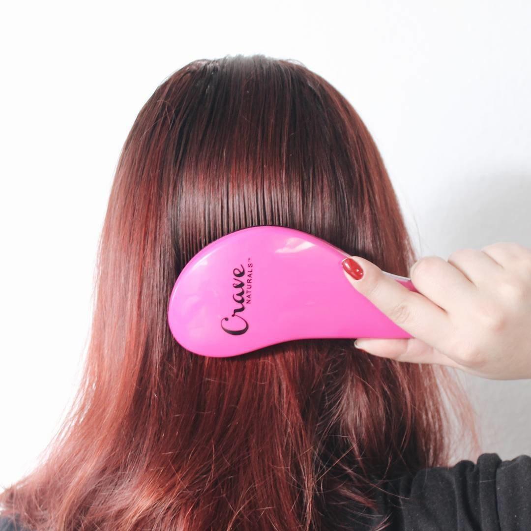 A person running a brush through their hair