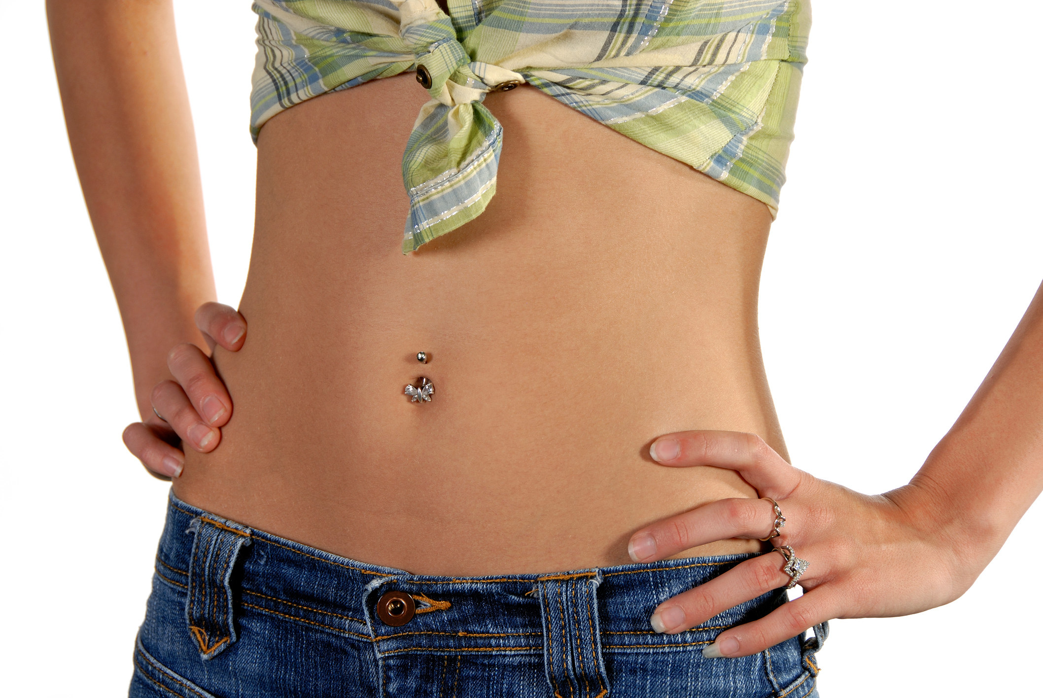 A photo of a woman in a tied up top and lowrise jeans exposing her pierced belly buttin