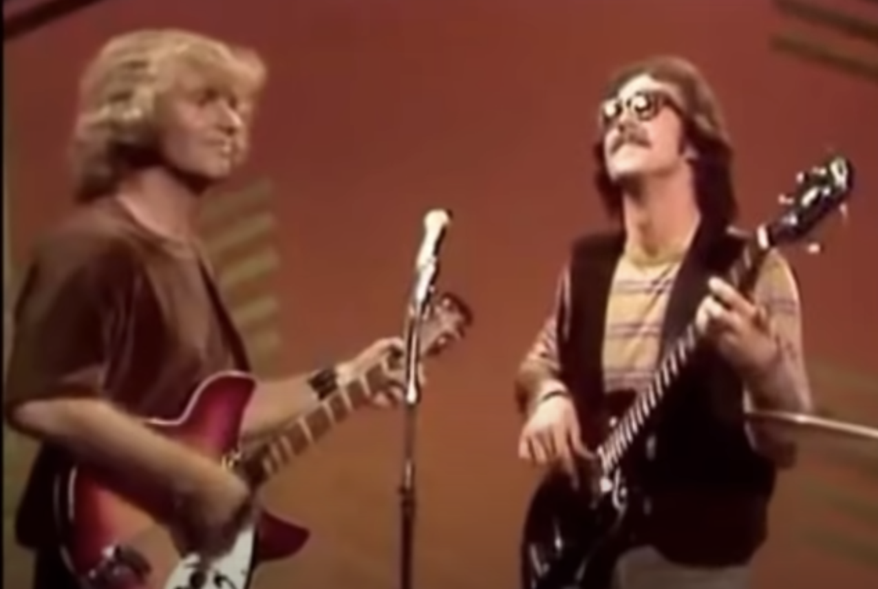 Creedence Clearwater Revival playing guitar and singing onstage