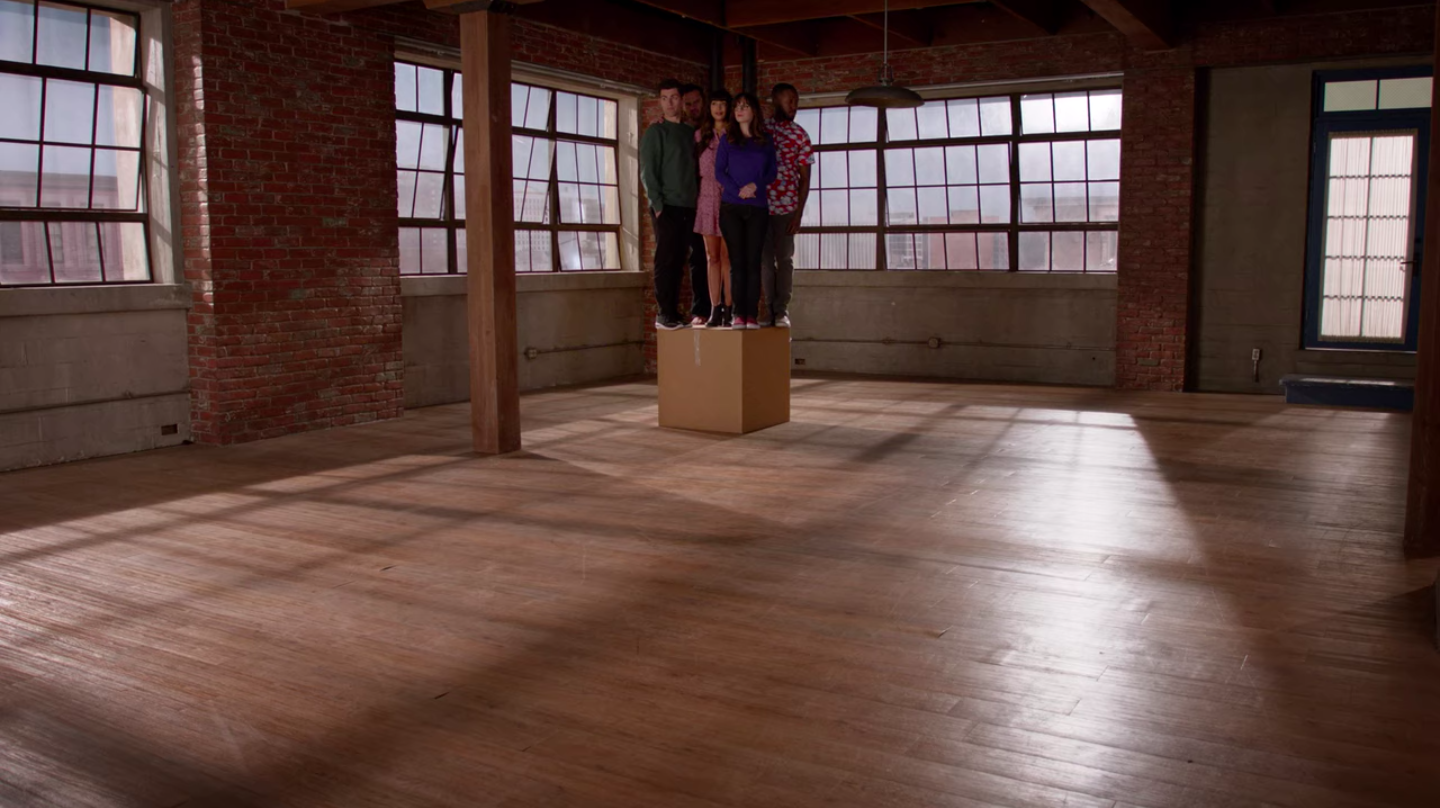 Everyone stands on one box, looking around the otherwise empty loft