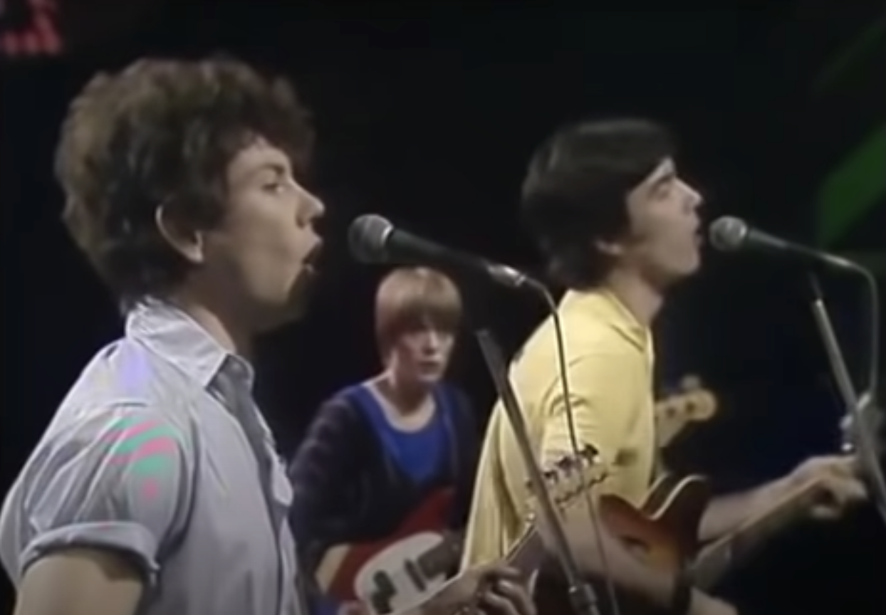 The Talking Heads onstage singing and playing guitar