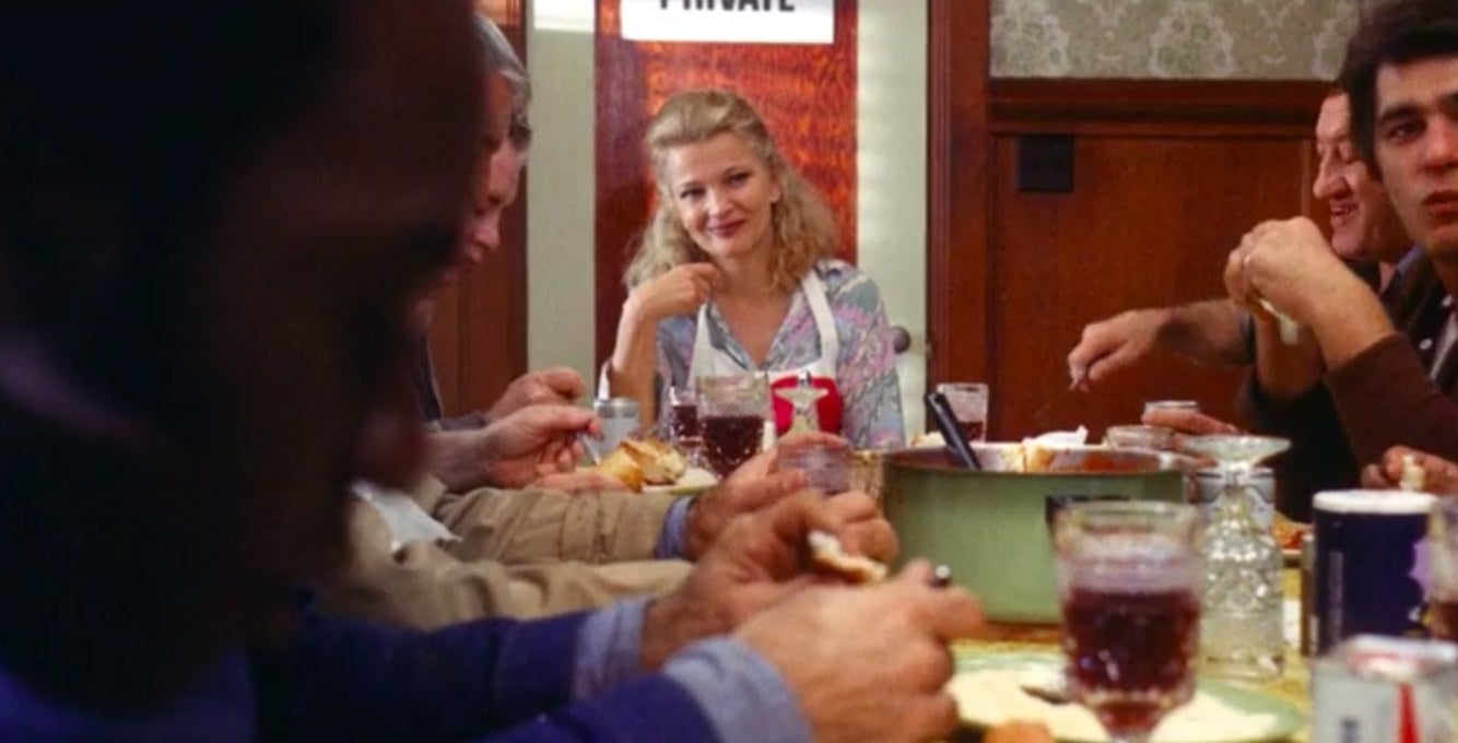 Gena Rowlands as Mabel Longhetti, sitting at a table full of family members in 'A Woman Under the Influence'