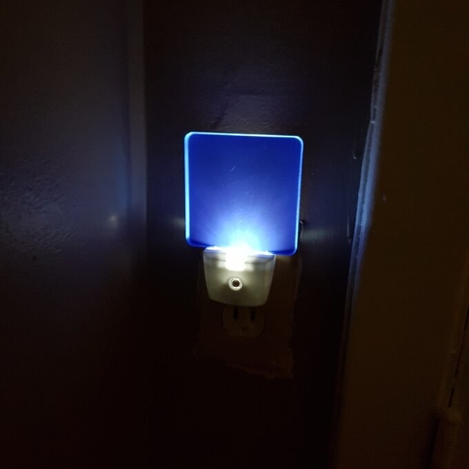 The nightlight in blue, illuminated in the dark and casting a bright light