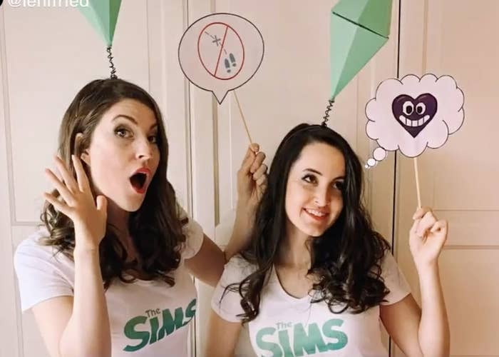 Two women wear the Sims game diamond over the heads