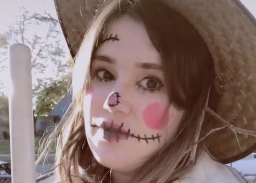 A woman wears makeup to look like a scarecrow and a straw hat