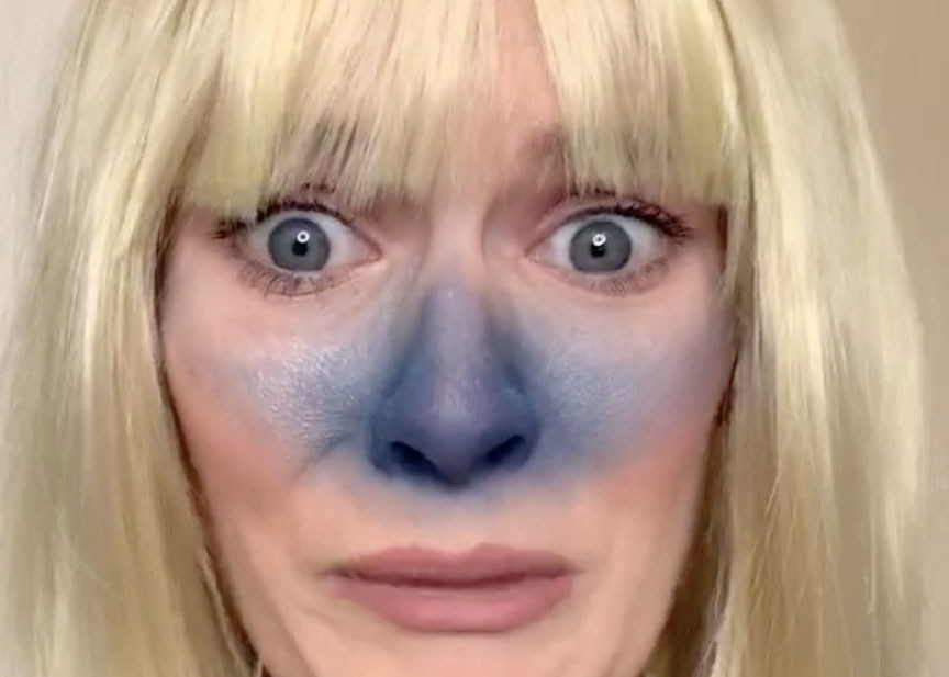 A woman wears a blonde wig and blue face paint over her nose
